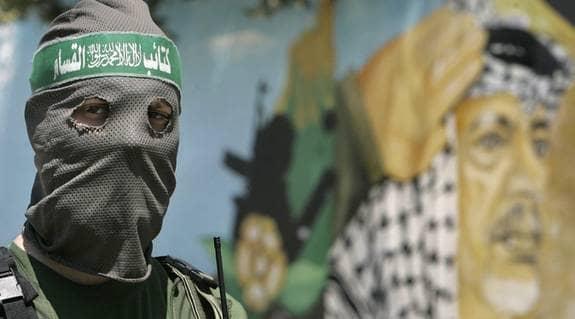 Vi måste minnas historien. En palestinsk militant från Hamas står på vakt framför en väggmålning av Fatahs tidigare ledare, Yasser Arafat, utanför president Mahmoud Abbas kontor som togs över av Hamas 16 juni. Foto: AP