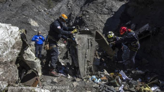 Räddningsarbetare går igenom vrakdelarna från det krachade planet. Foto: Bulls