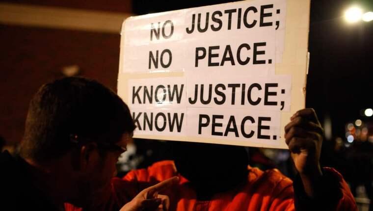 Det USA:s befolkning nu gör i Ferguson, New York, Chicago och Washington är en demokratirörelse. Men vi måste se bortom upploppen och brandröken för att förstå det, skriver Expressens Irena Pozar. Foto: Raffe Lazarian