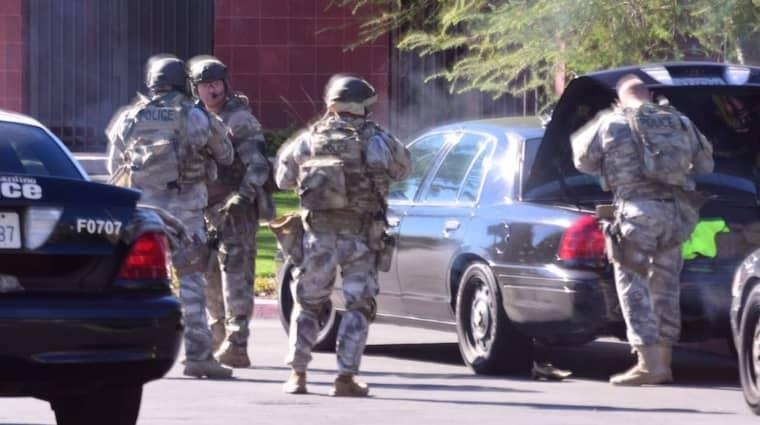 Tung beväpnad polis utanför socialcentret i San Bernadino. Foto: Doug Saunders/AP