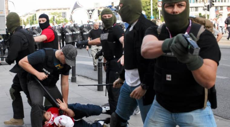 Polisen drar vapen under kravallerna.