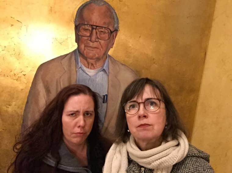 Martina och Gunilla framför ett porträtt av Jan Malmsjö.