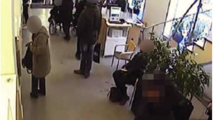 Kvinnan tar ut kontanter på banken, medan mannen iakttar henne. Foto: Polisen