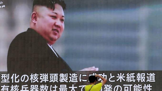 En man i Tokyo fotograferar ett tv-inslag som visar Nordkoreas ledare Kim Jong-Un. Foto: SHIZUO KAMBAYASHI / AP TT NYHETSBYRÅN