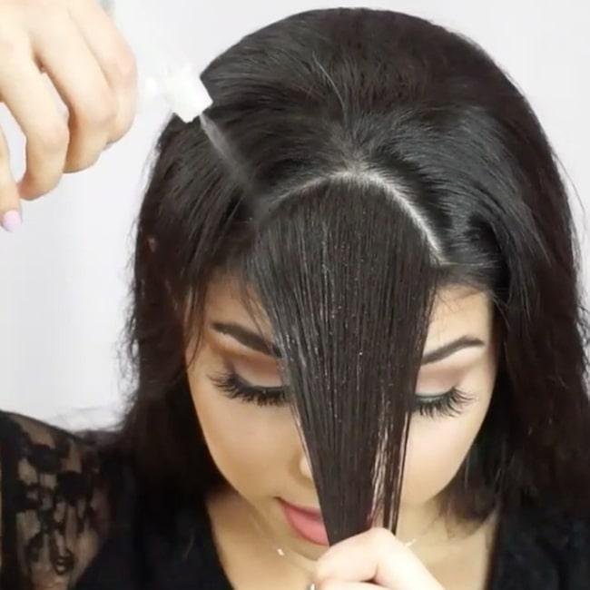 Camila börjar med att dela upp luggen i en sektion och spreja håret med  vatten. 2a1b4585923b0