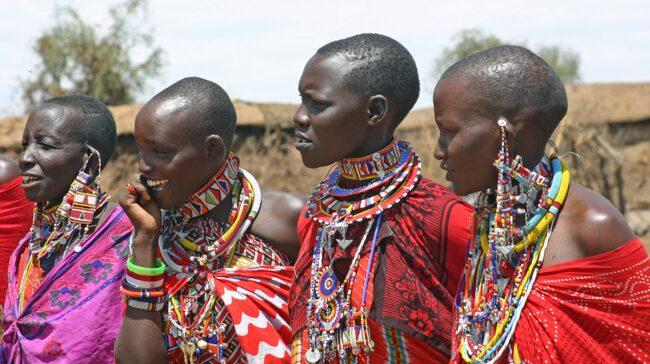 Traditionellt klädda masaikvinnor säljer smycken till turisterna i nationalparken Masai Mara.
