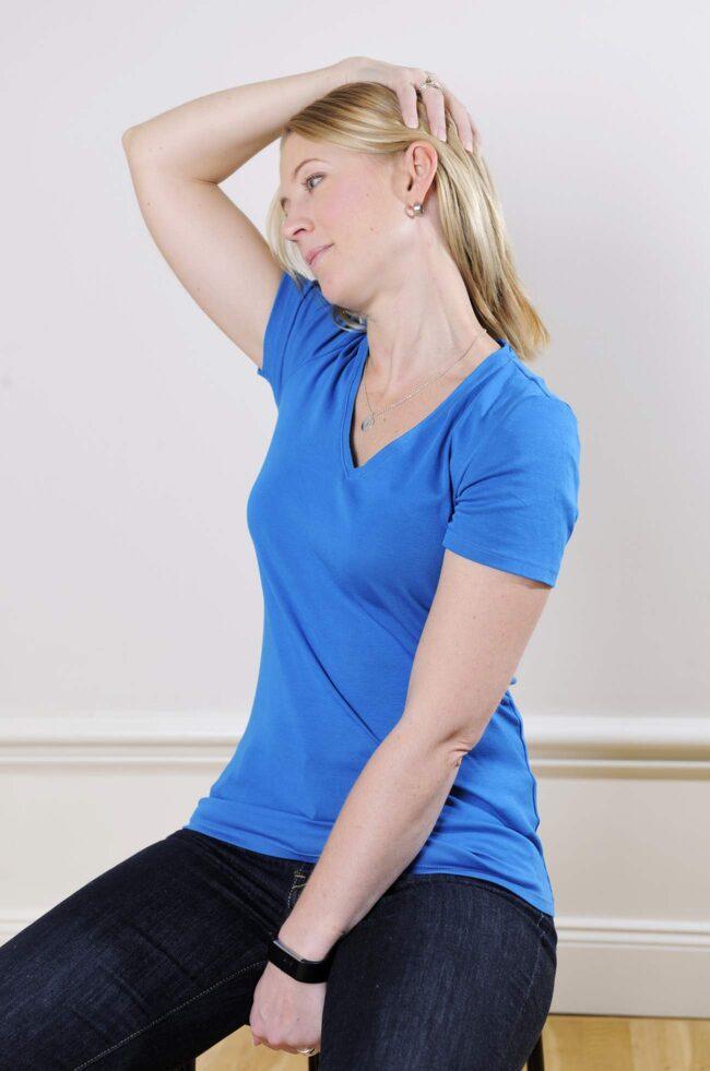 <strong>2. Sidan av nacken</strong><br>Ta tag med ena handen i framkanten av stolen. Ta tag om huvudet med andra handen. Luta dig bakåt, och vrid och luta huvudet bortåt från den hand som håller i stolen. Det ska kännas på sidan av nacken. Gör samma sak på andra sidan.