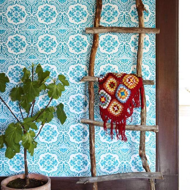 Trädgrenar. Denna charmiga stege är gjord av nedfallna trädgrenar och är fin att ställa mot en vägg, mest som prydnad. Tapet Azulejos från kollektionen Christian Lacroix, 830 kronor per rulle, Designers guild. Ponchon är köpt i Indien.