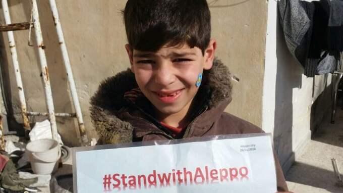 Souleyman Khalifa, 9, håller upp en skylt med hashtaggen #StandWithAleppo. Sjukhusen har slagits ut och maten börjar ta slut i östra Aleppo.