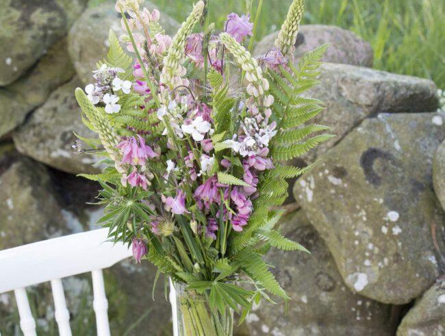 I den här buketten utgick vi från några långa lupiner och buketten fick då en hög form. Övriga blommor som vi har använt är flox, akleja, grässtrån, ormbunkar och fröställning från backsippa.