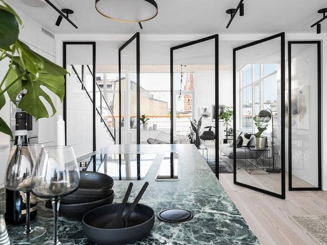 Det marmorinredda köket har glasdörrar in till vardagsrummet.