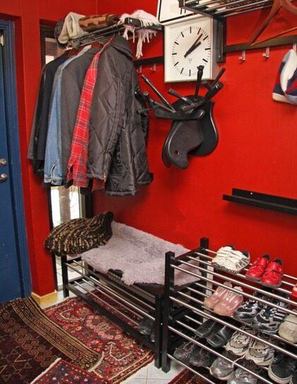 EFTER: organiserat. Fler hatthyllor och klädhängare, generöst med skohyllor där den ena också fungerar som en bänk att sitta på medan man knyter skorna gör det lätt att organisera kaoset. Älghuvudet som är gjort av en pinnstol fungerar också som en extra hatthylla. En varmt röd färg på väggarna och flera små persiska mattor på golvet gör hallen mer inbjudande och ombonad.
