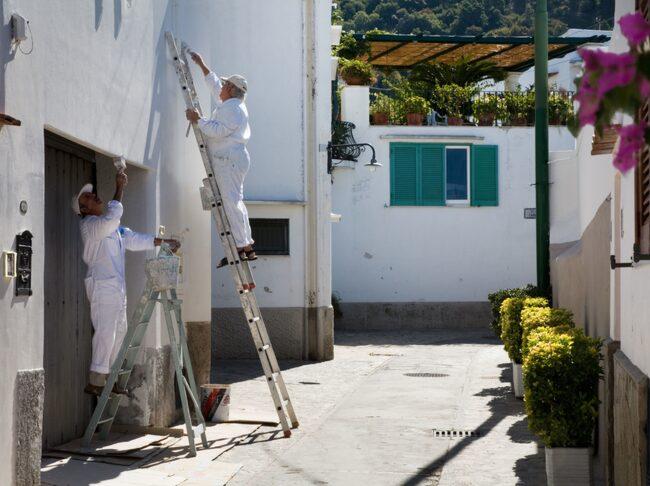 Två män som målar ett hus på Capri i Italien.