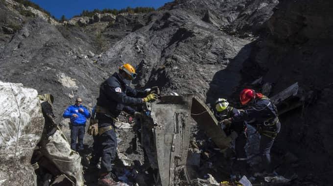 Här jobbar räddningsarbetare med att ta hand om spillrorna efter plankraschen.