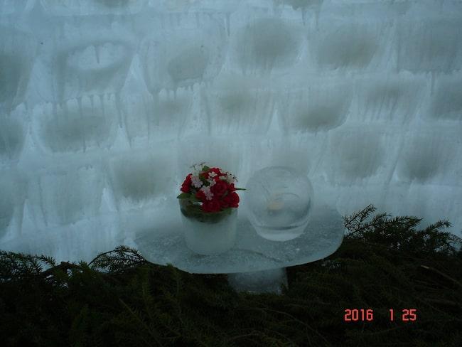Inne i igloon har Janne byggt ett isbord som han dekorerat med blommor i en isvas. Golvet är täckt med barr.