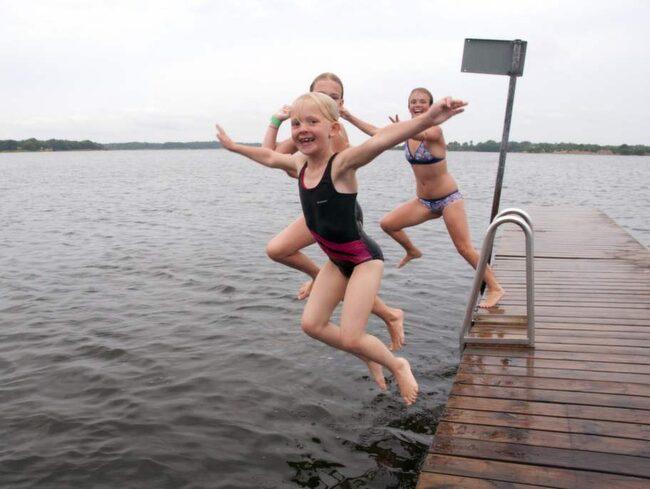 Glada badtjejer hoppar från bryggan på Sturkö gång på gång.