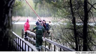 Här drar polisen upp den döda kroppen ur vattnet.