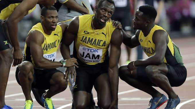 Lagkamraterna är framme för att hjälp Usain Bolt. Foto: DAVID J. PHILLIP / AP TT NYHETSBYRÅN