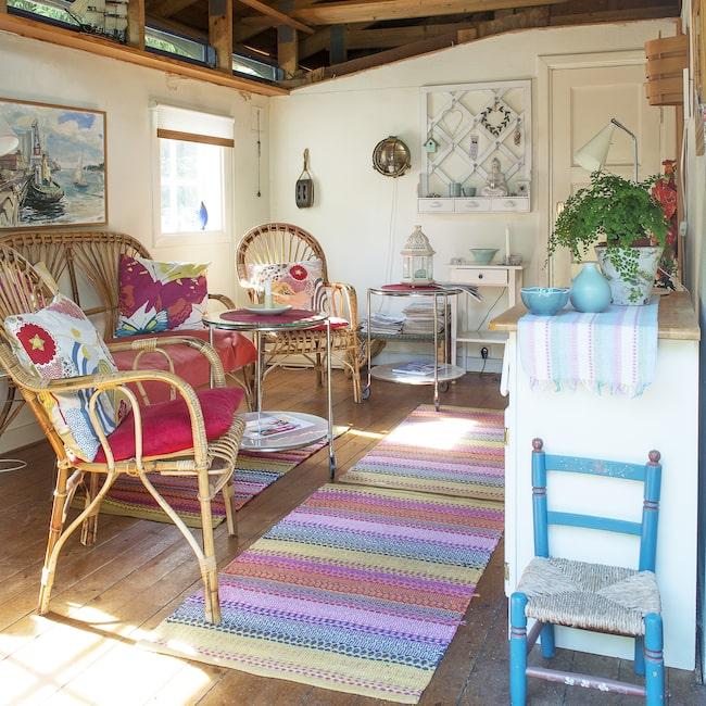 I det lilla huset får allt som behövs för ett avslappnat sommarliv plats. Praktiska rottingmöbler som kan tas ut vid behov står i allrummen som är inrett med färgglada textilier i blå och rosa nyanser.