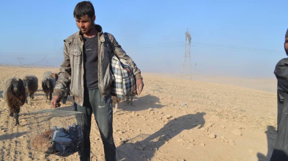 Den här mannen tog med sig en bur med fåglar när han tvingades lämna sitt hem.