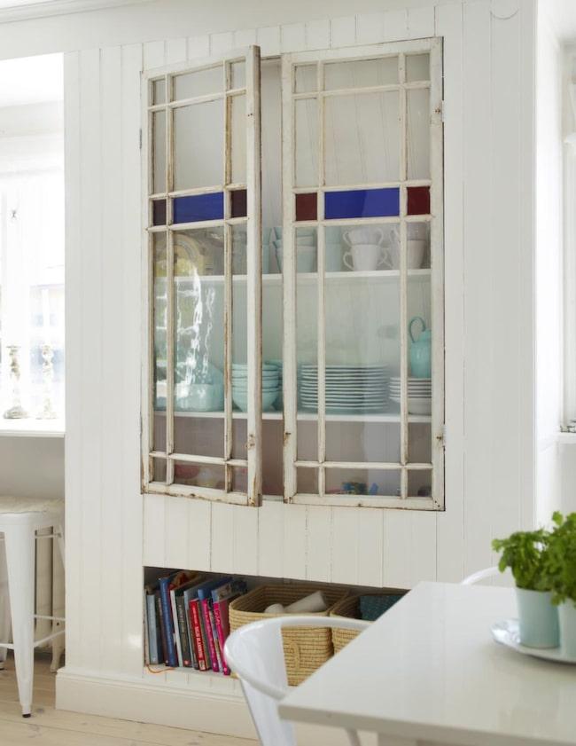 Serveringsskåp. Av de här två vackra fönstren byggdes ett större skåp för porslinet i köket. En passande plats valdes ut i köket, skåpets mått utgick från de förutsättningar som fanns. Väggarna byggdes med hjälp av reglar som sen förseddes med pärlspont på både utsida och insida. Alltsamman målades i vitt. Till sist sattes de två fönstren dit på gångjärn som dörrar, att de är lite nötta och avskavda bidrar bara till charmen. Insidan på skåpet inreddes med rejäla hyllplan som sattes upp på lister.