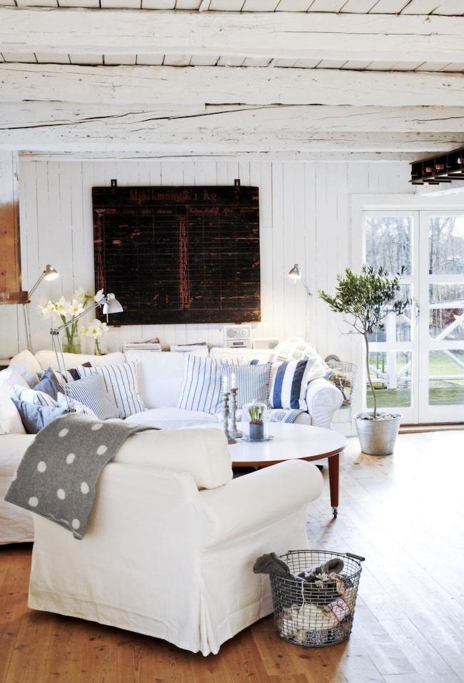 <strong>Soffgrupp</strong><br>På väggen ovanför den vita hörnsoffan från Ikea hänger en gammal mjölkningstavla från säteriets ladugård. Sädespelarna från loftet för tankarna till tiden då huset var ett magasin. Zinkföremålen finns hos Butik Stora Holm. Kuddar från Nyblom Kolléns vårkollektion. Prickig Klippanpläd. Lamporna på fot är från Ikea. Korgen med garn är handgjord och av märket Korbo.