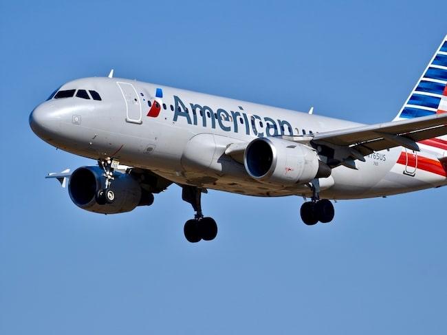 Passageraren på American Airlines köpte biljett i affärsklass, för att bjuda kompisarna på gratis sprit i ekonomiklassen.