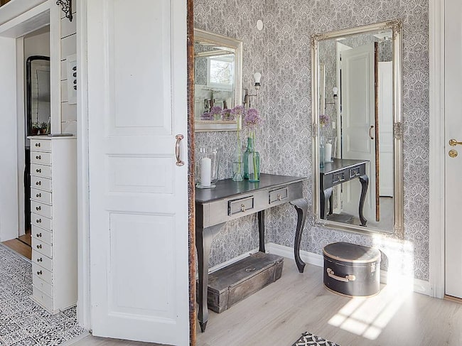 Hall med plats för avhängning. Ljust laminatgolv samt tapetserade väggar och målad träpanel på väggar.